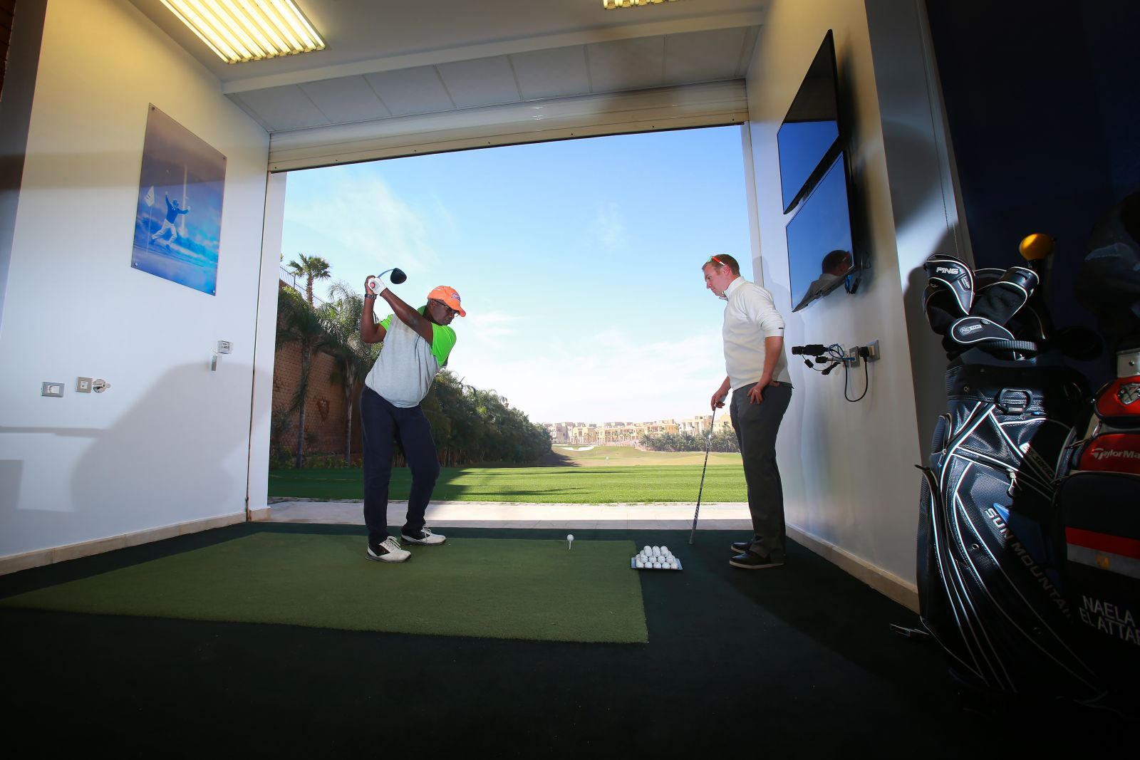 An instructor watches a student at The Allegria golf academy